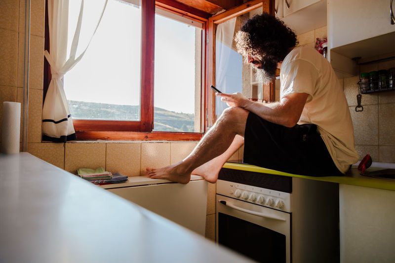 Man using mobile phone in kitchen at home