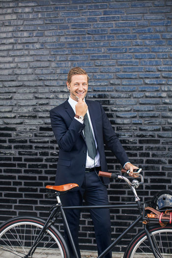 Portrait of a smiling young man holding bicycle against brick wall