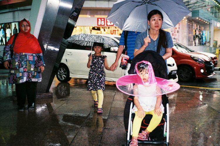 Full length of a girl standing on wet street in city