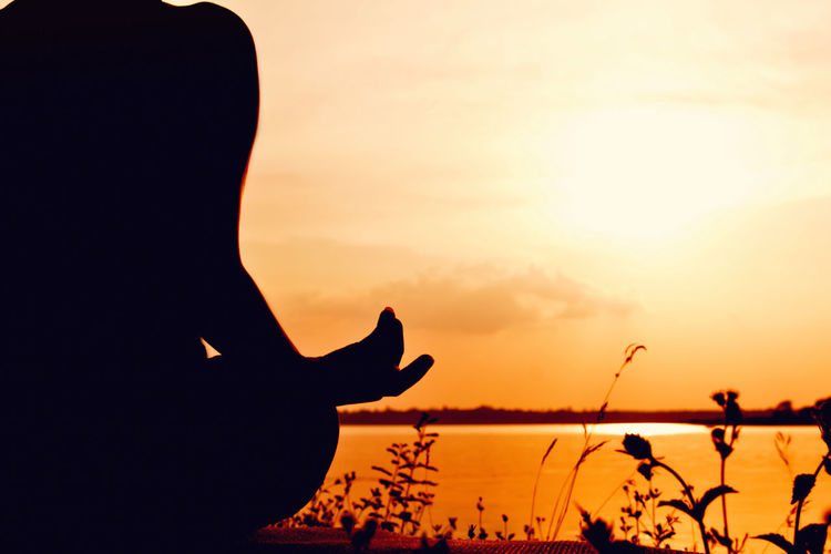 Silhouette Of Woman Doing Yoga Against Sky During Sunset