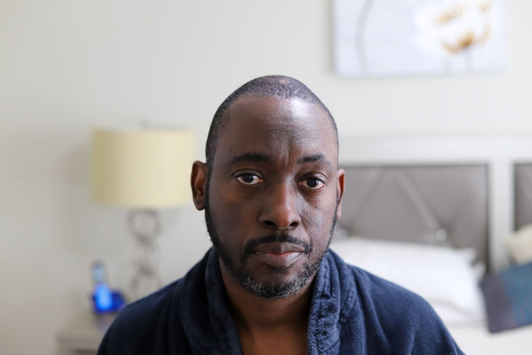 A portrait of a african-american man sitting on a bed and looking sad and depressed
