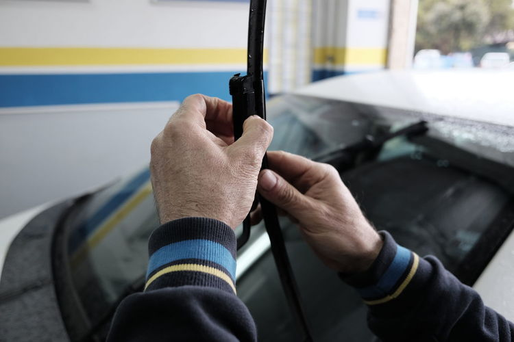 Cropped hands of mechanic holding windshield wiper against car at auto repair shop