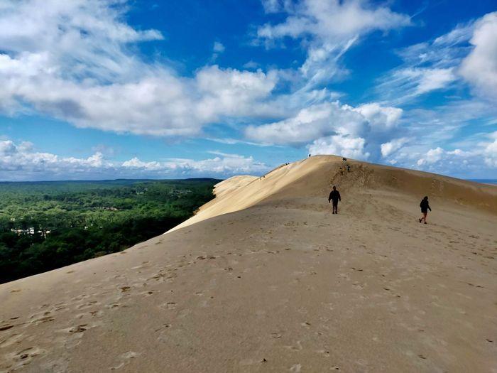 Rear view of people walking on desert land against sky