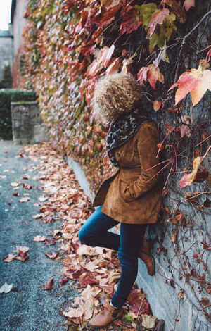 Adult Autumn Curly Hair Day Full Length Girl Leaf One Boy Only One Person Outdoors People Plants Real People Wall Warm Clothing Fashion Stories