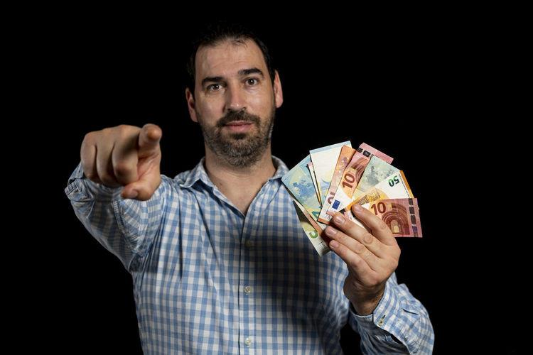 Portrait of mature man holding camera against black background