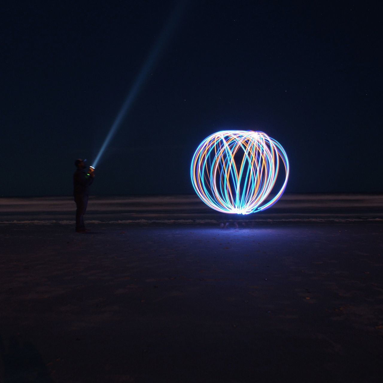 Side view of silhouette man with torch standing in front of wire wool at night