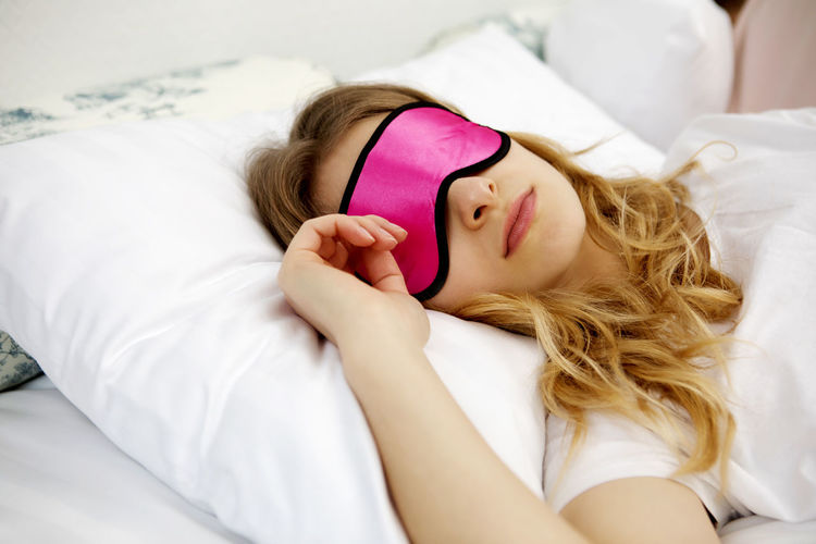 Close-Up Of Woman Sleeping On Bed At Home