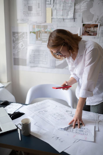 Midsection of woman working with smart phone on table