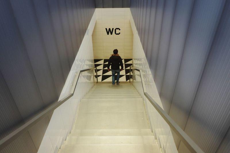 Rear view of a man walking in corridor