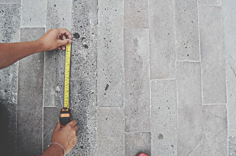 Person measuring a wall