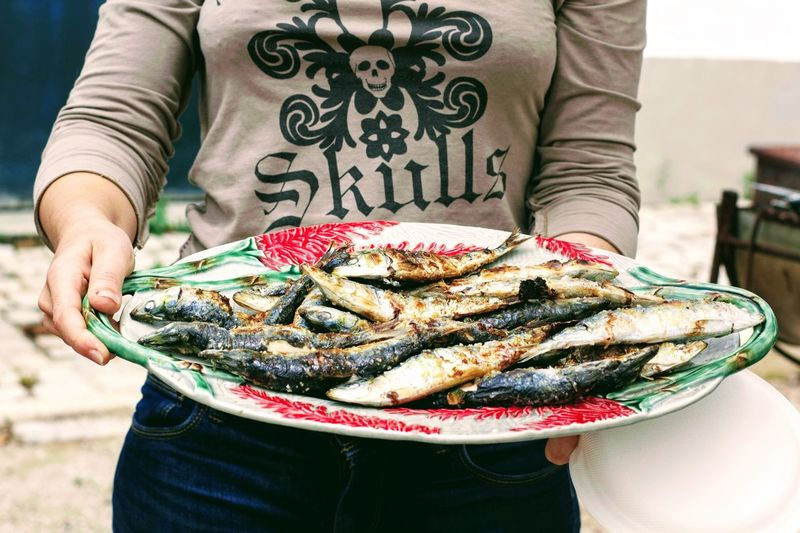 Midsection of woman holding sardines