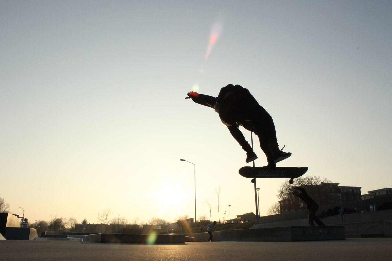 mid-air, jumping, full length, real people, motion, sunset, one person, clear sky, leisure activity, vitality, skill, lifestyles, stunt, outdoors, silhouette, men, extreme sports, sport, sky, flying, skateboard park, nature, stunt person, day, adult, people