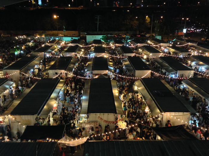 High angle view of people in illuminated flea market at night