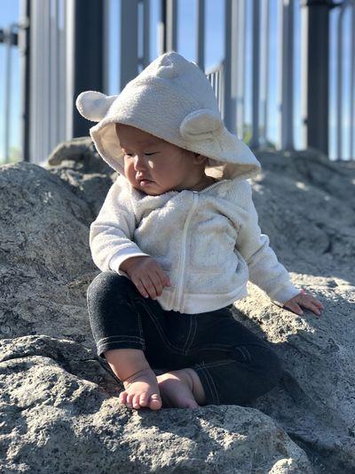 Full length of cute baby girl sitting on rock