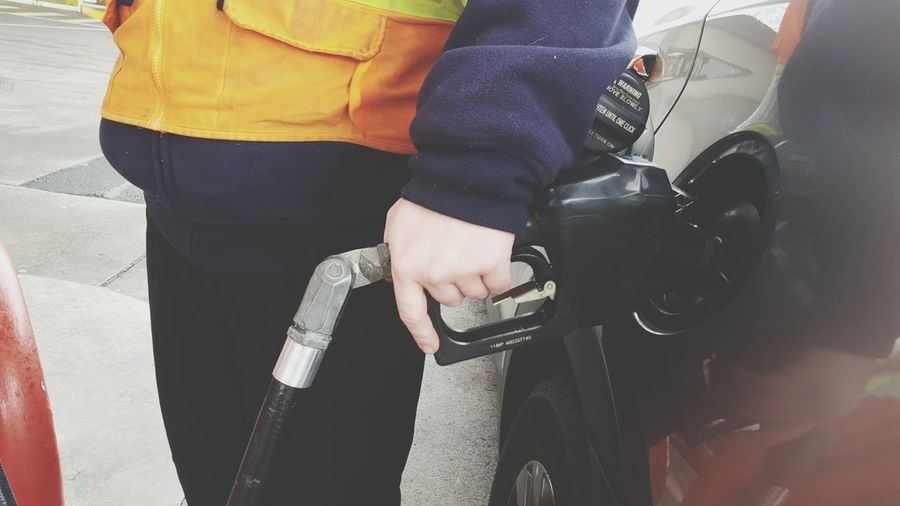 Midsection Of Man Refueling Gasoline In Car At Gas Station