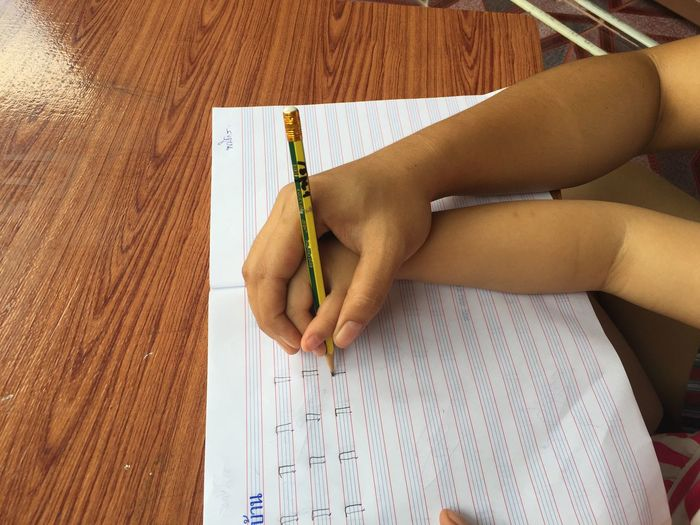 Cropped Hand Of Person Teaching Child To Write