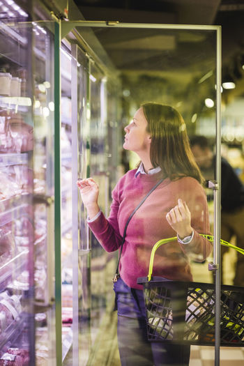 Side view of woman standing in store