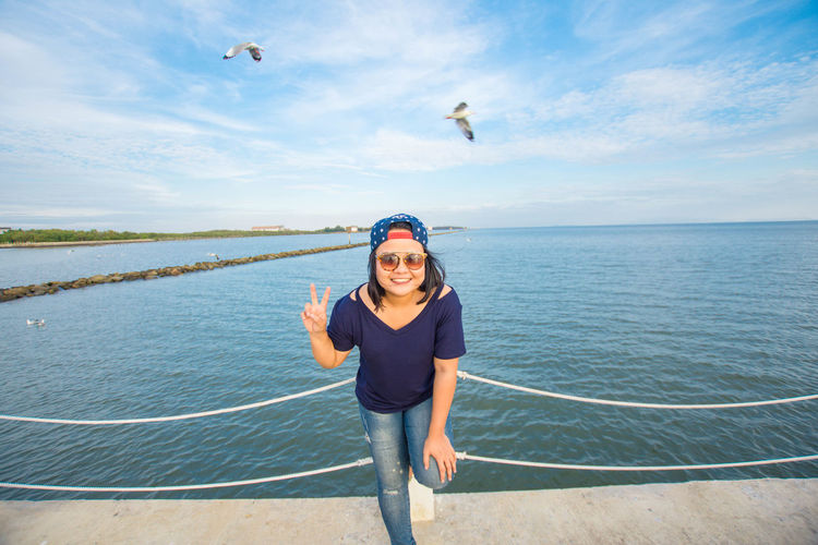 Portrait of smiling mid adult woman gesturing victory sign against sea and sky