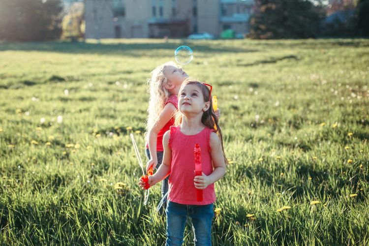 Girls on field against sky