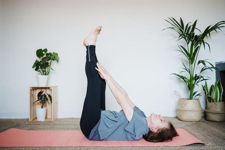 Senior woman stretching at home