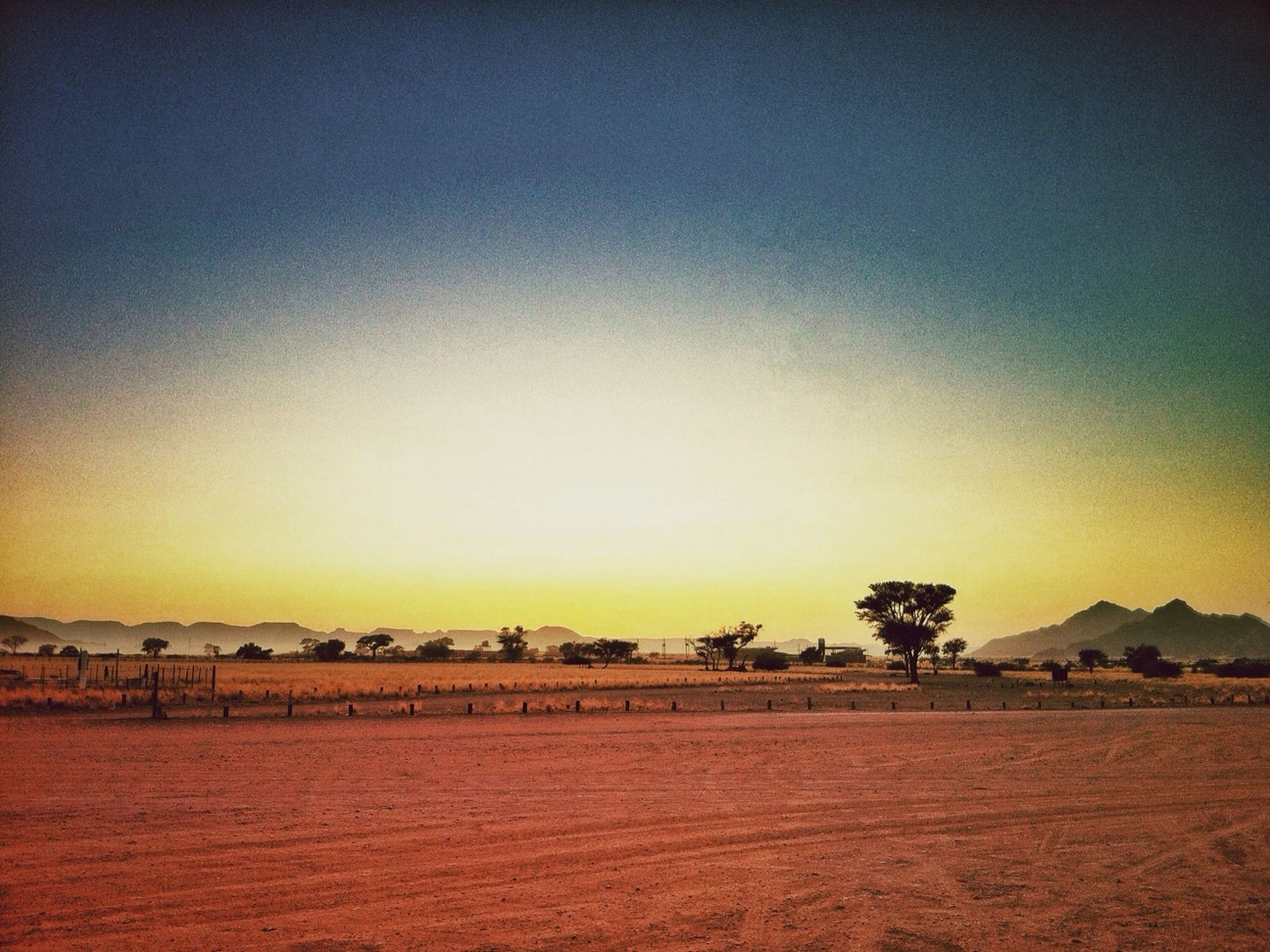 sunset, copy space, orange color, tranquil scene, clear sky, tranquility, scenics, landscape, built structure, beauty in nature, architecture, nature, building exterior, idyllic, sand, sky, outdoors, remote, no people, field