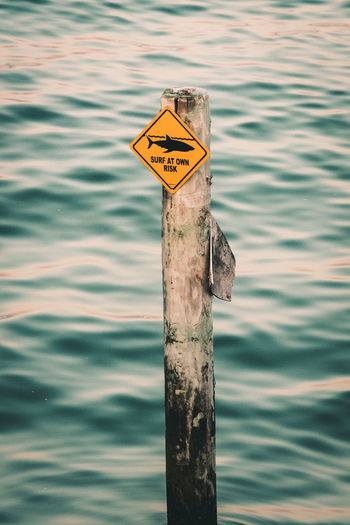 Close-up of sign on wooden post in lake