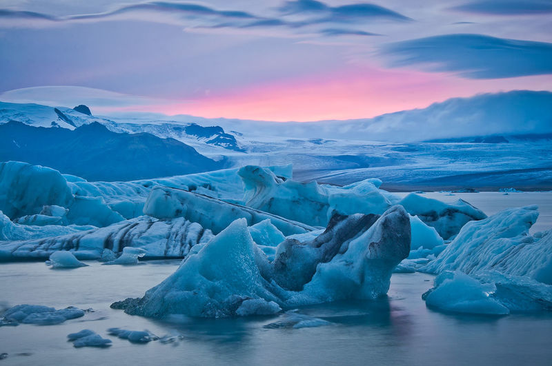 Icebergs in frozen lake against cloudy sky at sunset