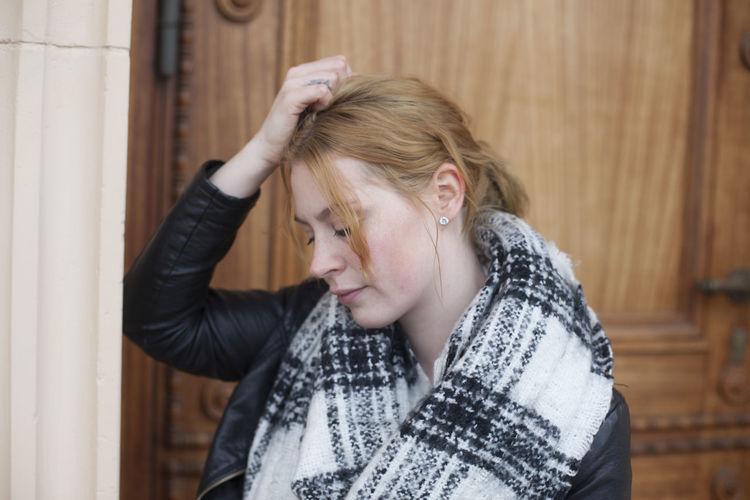 Sad Woman Standing Against Wooden Door