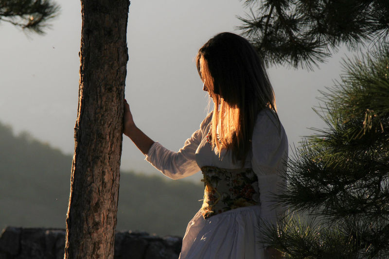 Side view of young woman standing by tree against sky