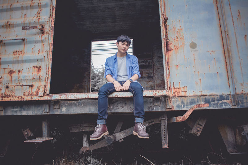 Low angle portrait of sad young man sitting on abandoned freight train