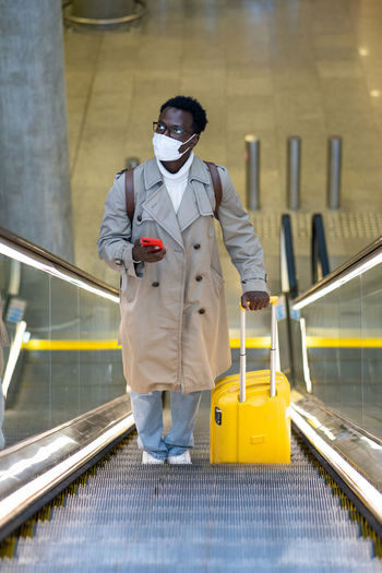 Side view of toy man wearing mask standing on escalator
