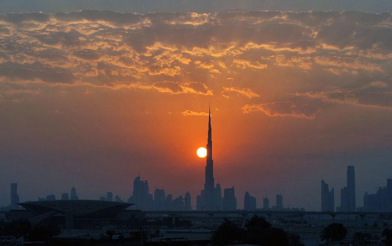 Dubai skyline against cloudy sky during sunset