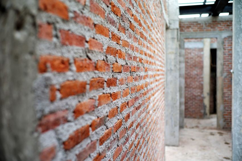 Perspective of brickwork wall and structure of house under construction. Reinforcement Cement Concrete Bricklayer Site Construction Building Raw Perspective Architecture Built Structure Brick Brick Wall Wall - Building Feature Building Exterior Building No People Wall Day Pattern Outdoors Abandoned Close-up Entrance Focus On Foreground Corridor Metal