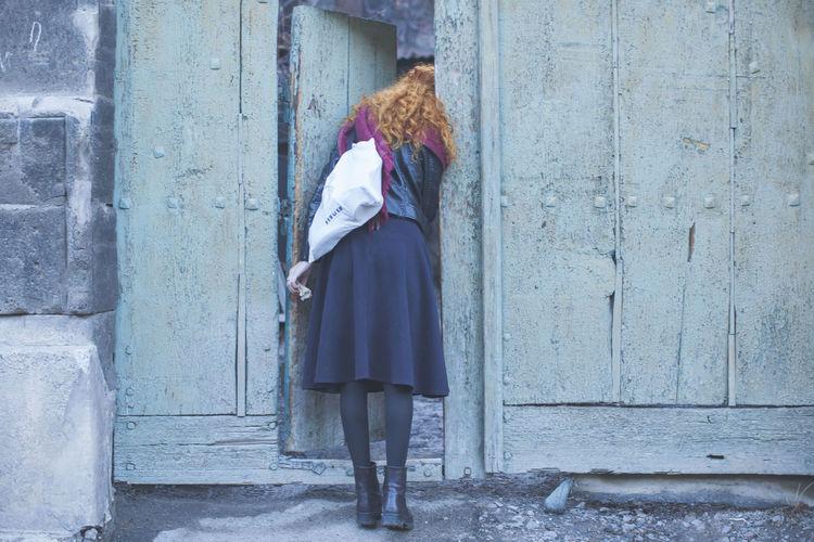 Rear View Of Woman Peeping Through Old Door