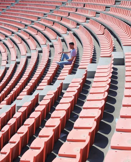 High angle view of man sitting on bleacher at stadium