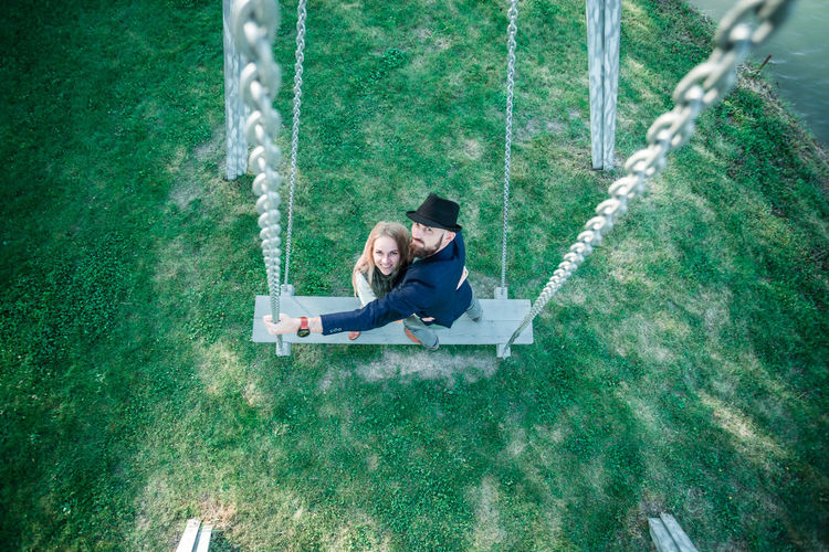 High angle view of couple standing on swing at park