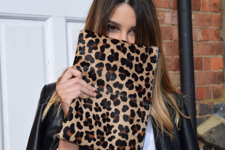 Portrait of woman with long hair holding cheetah print purse