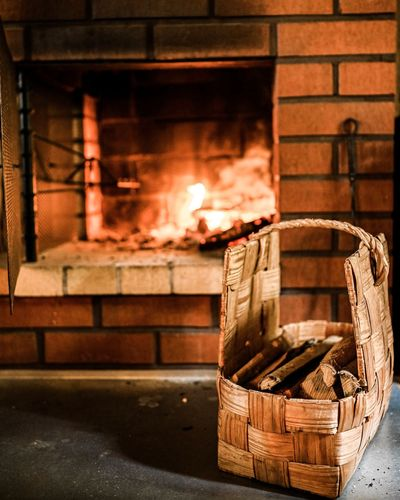 Firewood in wicker basket on table against fireplace at home