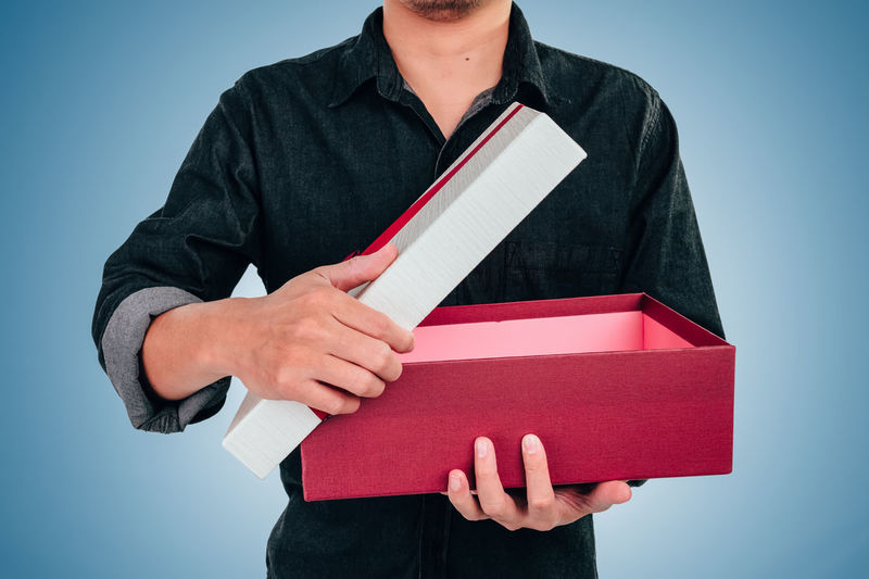 Midsection of man holding book against gray background