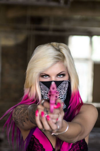 Portrait Of Young Woman With Covered Face Aiming Pink Gun