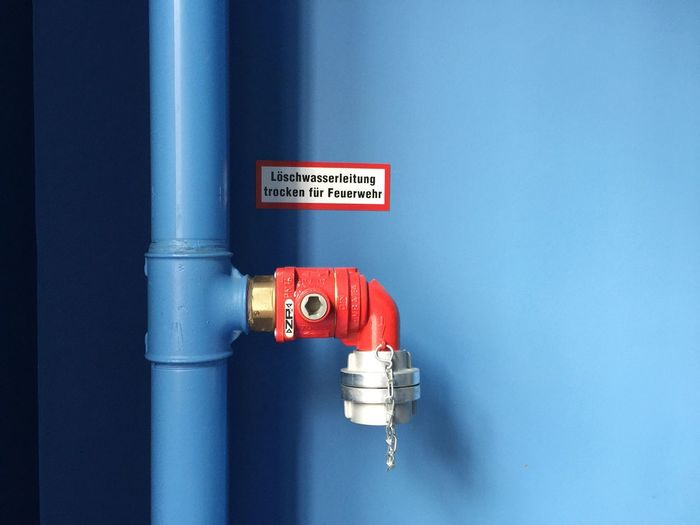 Close-up of pipe against blue wall