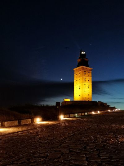Lighthouse by illuminated building against sky at night