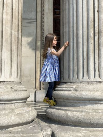 Side view of girl standing on column