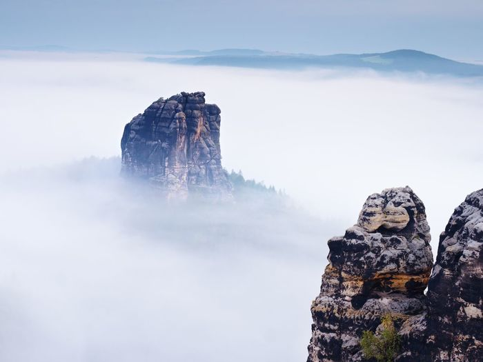 Sharp sandstone rock empire sticking out from heavy fog. deep misty valley full of creamy mist.