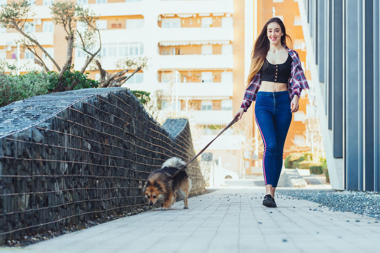 Woman walking with dog on footpath