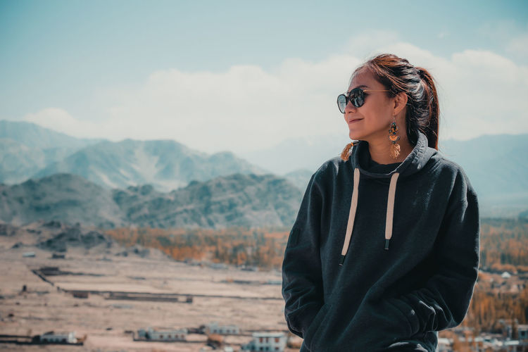 Smiling woman looking away against mountains