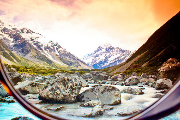 Scenic view of stream by mountains against sky during sunset seen through glass