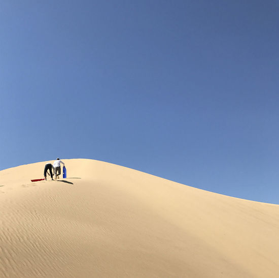 Low angle view of people walking at desert against clear blue sky