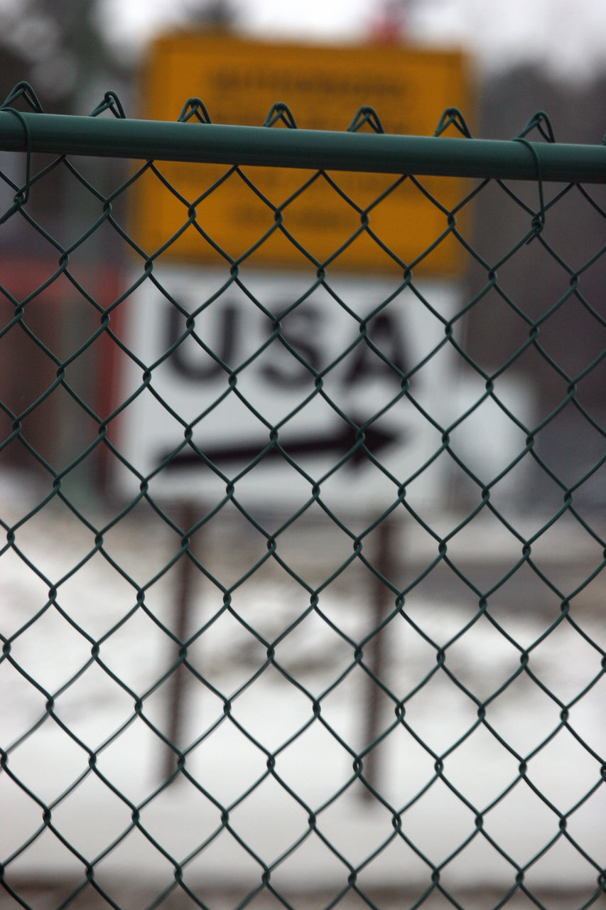 Close-Up Of Chainlink Fence Against Sign Board