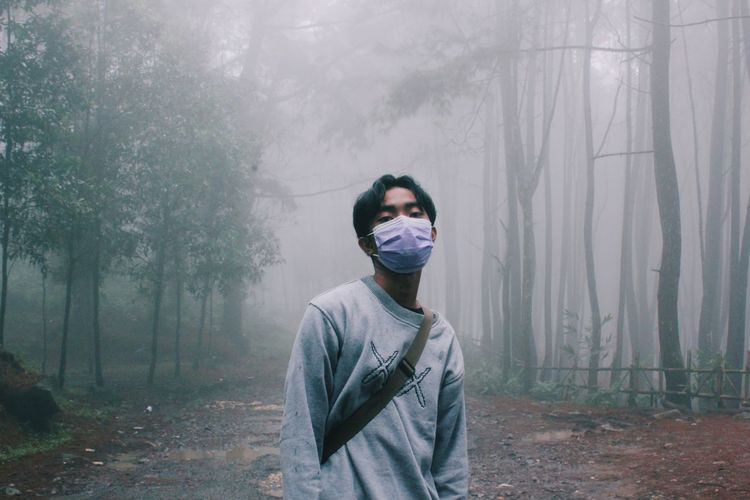 Portrait of young man wearing mask standing in forest